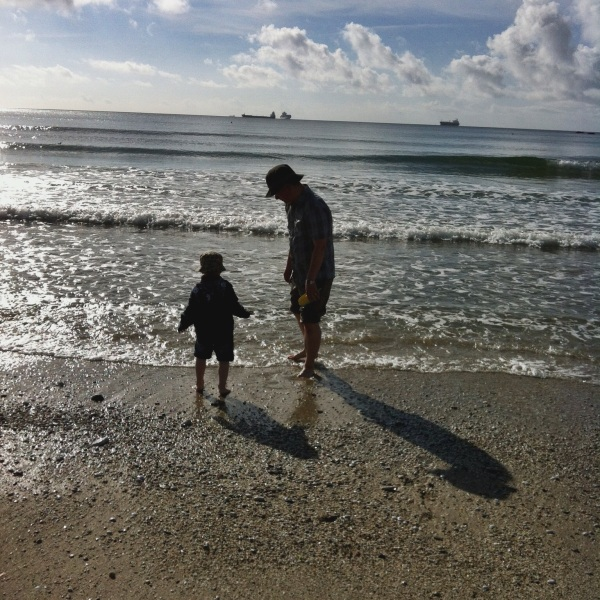 Father and son paddling in the sea